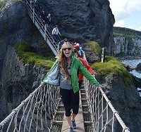 Counsellor Brianna standing on a rope bridge by the sea